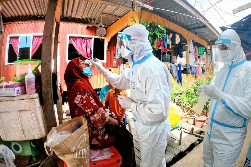 A Ministry of Health worker carrying a nose swab to a resident in house-to-house Covid-19 screening in Sandakan, Sabah.