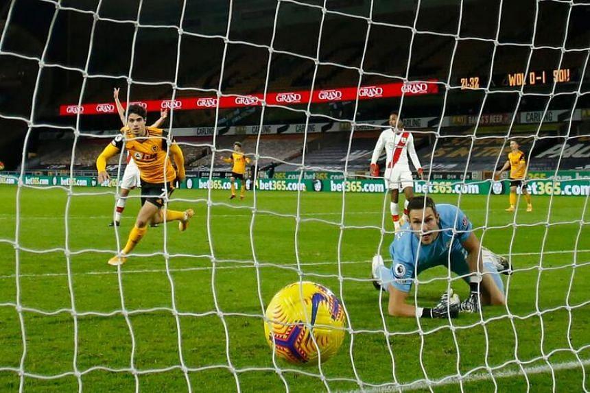 Wolverhampton Wanderers' Portuguese midfielder Pedro Neto (left) scores their first goal past Southampton's English goalkeeper Alex McCarthy on Nov 23, 2020.
