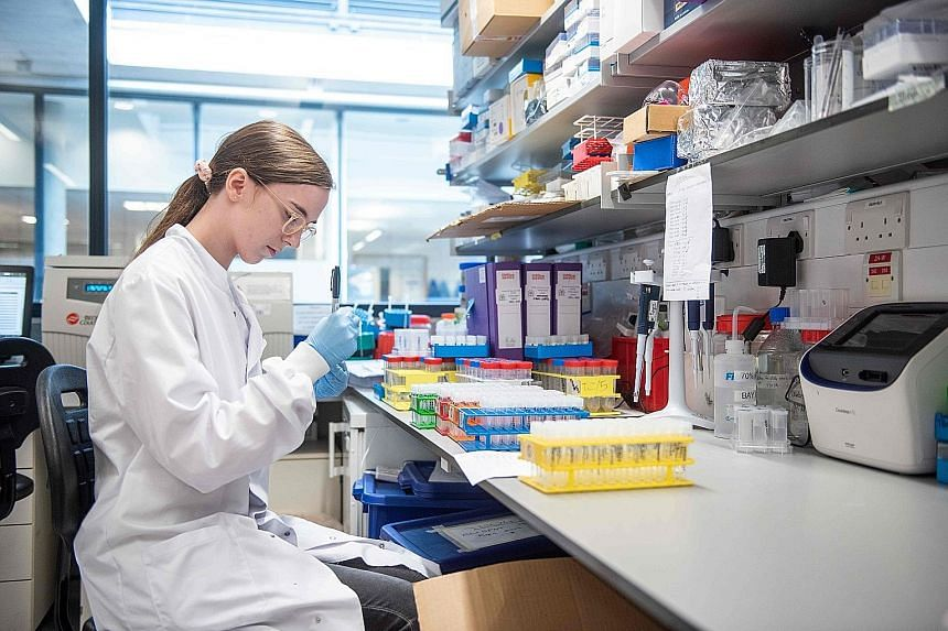 """A technician working on the University of Oxford's Covid-19 candidate vaccine. The announcement of a vaccine may drive market optimism, but does not reopen economies for now. """"The vaccine gives more of a vision for what may be late next year, and wha"""