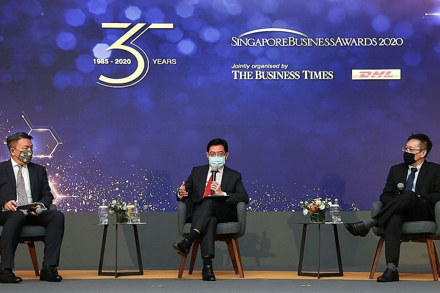 Deputy Prime Minister Heng Swee Keat speaking at the 35th Singapore Business Awards, held at Singapore Press Holdings' News Centre auditorium yesterday. His fellow panellists were DHL Express Singapore managing director Christopher Ong (left) and Bus
