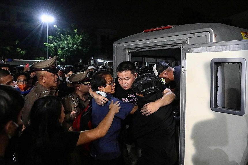 Pro-democracy activist Parit Chiwarak being helped out of a police van as it arrived at a police station in Bangkok on Oct 30, after he was released from jail over protest-related offences.