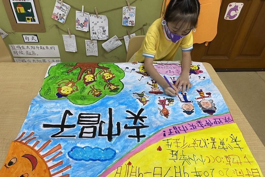 A child creating posters for a Chinese theatre production, as part of a learning technique taught under LSH's Pedagogy for Enhanced Mandarin Acquisition programme. PHOTO: LITTLE SKOOL-HOUSE