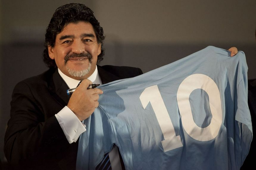 Diego Maradona holds a SSC Napoli number 10 jersey in Naples, on Feb 26, 2013.