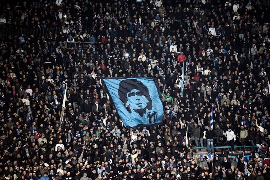 SSC Napoli's fans display a flag with the effigy of former player Diego Maradona at San Paolo Stadium in Naples, on Jan 7, 2013.
