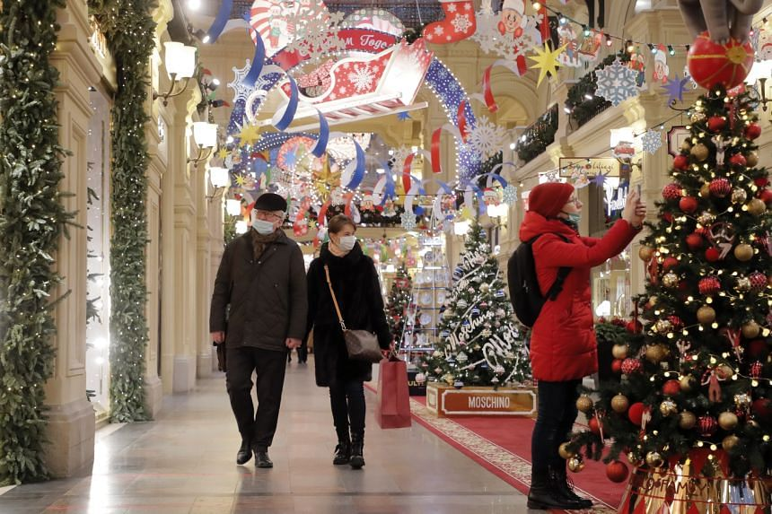 People walk in the luxury GUM department store on the Red Square in Moscow, on Nov 25, 2020.