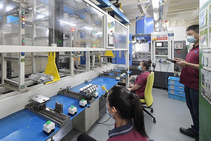 Staff at work at precision engineering firm Globaltronic Precision. Only the precision engineering and biomedical clusters saw growth last month. Precision engineering output was up 10.6 per cent from the same period a year ago. ST FILE PHOTO