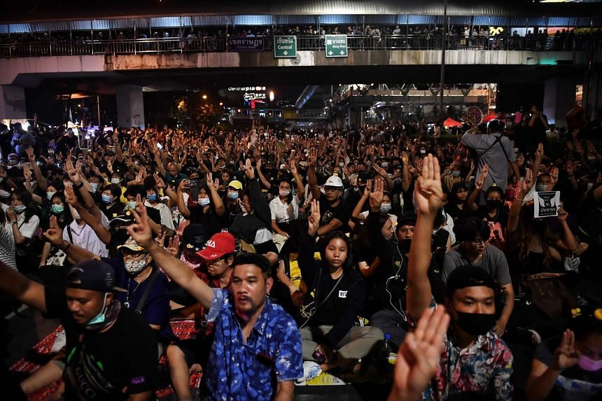 Pro-democracy protesters hold up the three-finger salute during an anti-government rally in Bangkok, on Nov 27, 2020.