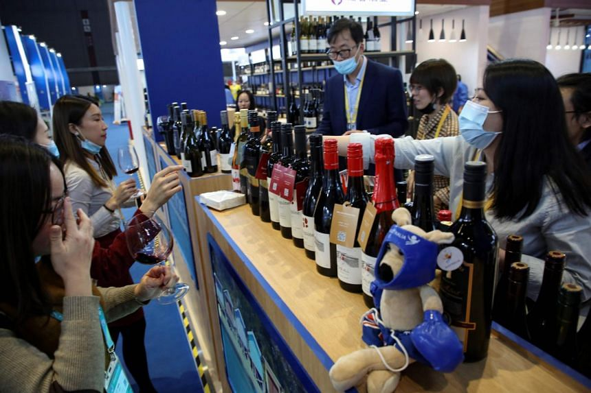 People taste red wine from Australia at the Food and Agricultural Products exhibition at the third China International Import Expo in Shanghai on Nov 5, 2020.
