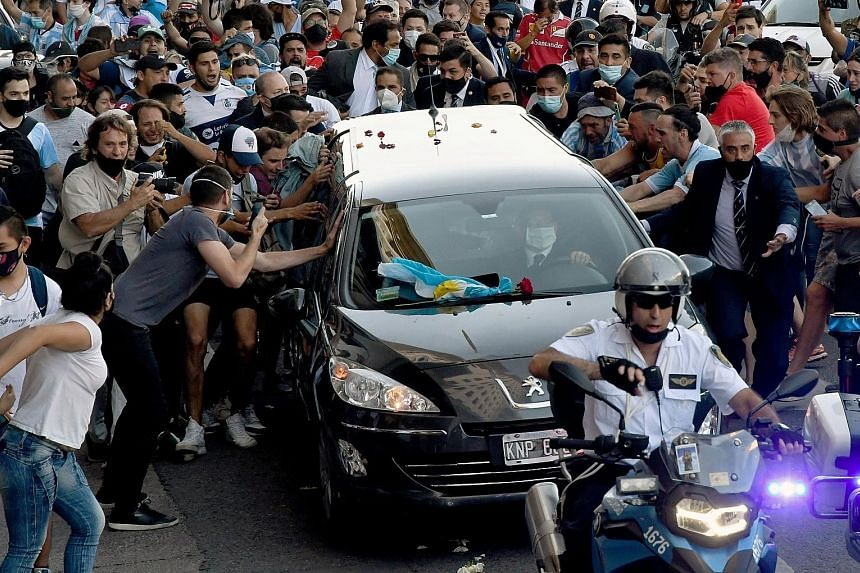 Left: Fans swarming around the hearse carrying Argentinian football legend Diego Maradona as it made its way from the Casa Rosada presidential palace in Buenos Aires to the cemetery on Thursday. Below: The hero's casket being carried at the Jardin Be