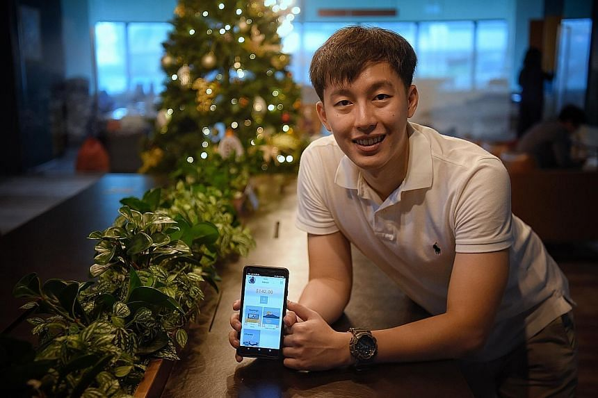 Taby Technologies co-founder Yap Jun Yi with the company's personal finance app. ST PHOTO: MARK CHEONG