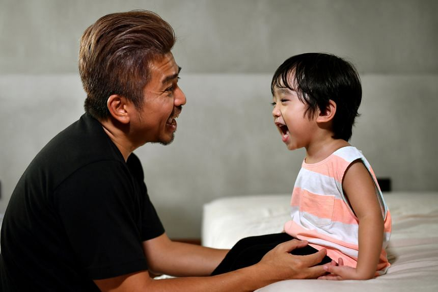 Stay-at-home dad Adrian Sim Wei Lim, 43, conversing with his son Rei Shen Yuxiang, two, at home.