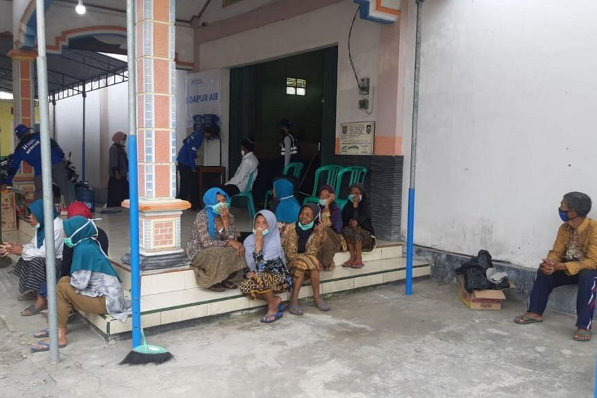 Ms Tasri (in grey veil) along with her neighbours, staying in a temporary shelter in anticipation of Mount Merapi's eruption.