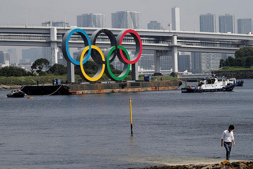 Boats towing the giant Olympic rings, which were removed for maintenance, at the waterfront area in Odaiba Marine Park in Tokyo in August. The shift to next year has caused logistical headaches, but is far less painful than cancelling it, with sponso