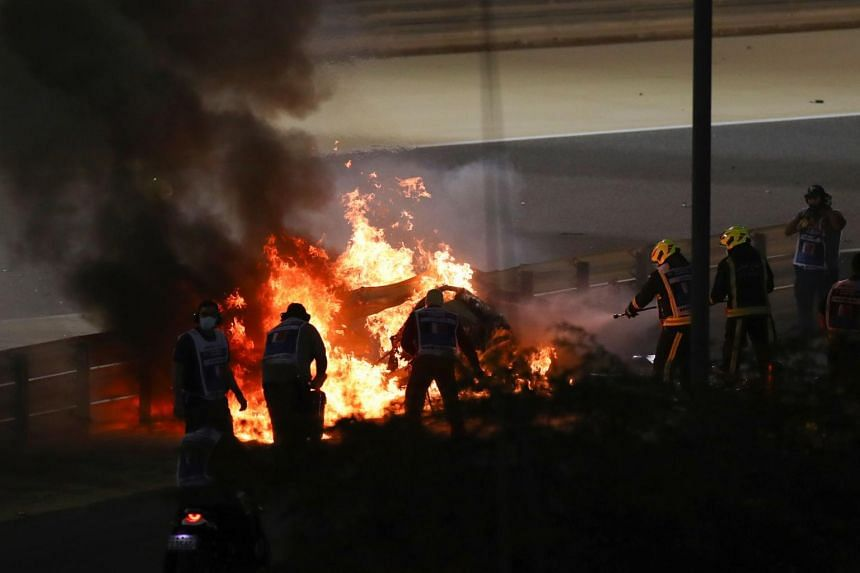 Fire marshals put out a fire on Haas F1's French driver Romain Grosjean's car during the Bahrain Formula One Grand Prix on Nov 29, 2020.