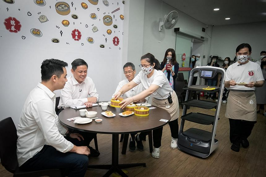 A Swee Choon staff member serving Minister for Trade and Industry Chan Chun Sing (second left) and Swee Choon owners Tony Ting (centre) and Ernest Ting (left) from a robot waiter, on Nov 30, 2020.