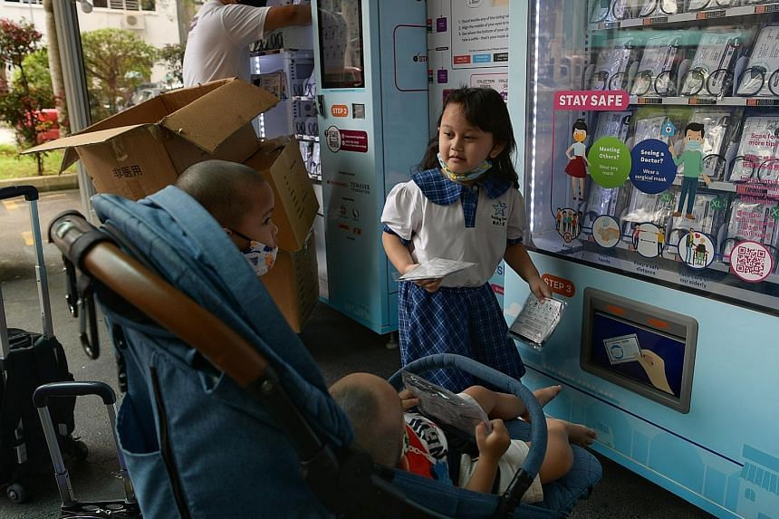 Kaysha Zulaikha, five, collecting masks with her siblings at the Bukit Panjang Community Centre yesterday. The masks are available in four sizes - small, medium, large and extra large - with the small ones intended for children under eight.