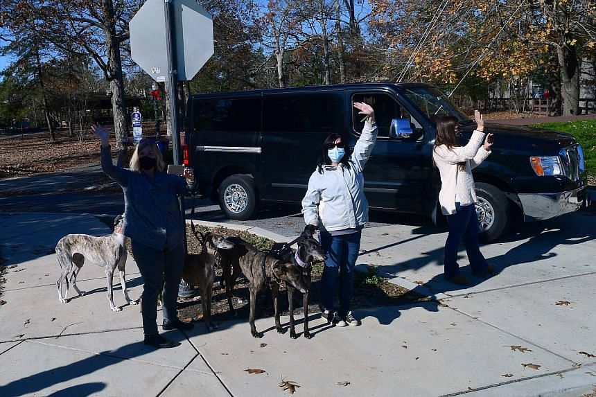 Supporters waving at President-elect Joe Biden's motorcade in Delaware on Sunday. Mr Biden's economic selections have been the subject of a battle between Democratic centrists - who mainly want a return to expertise and competence - and progressives