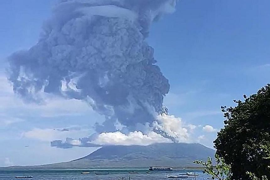 Residents gathering to watch as Mount Ili Lewotolok erupted on Sunday, sending a thick tower of debris 4km into the sky, in Indonesia's East Nusa Tenggara province. PHOTO: AGENCE FRANCE-PRESSE