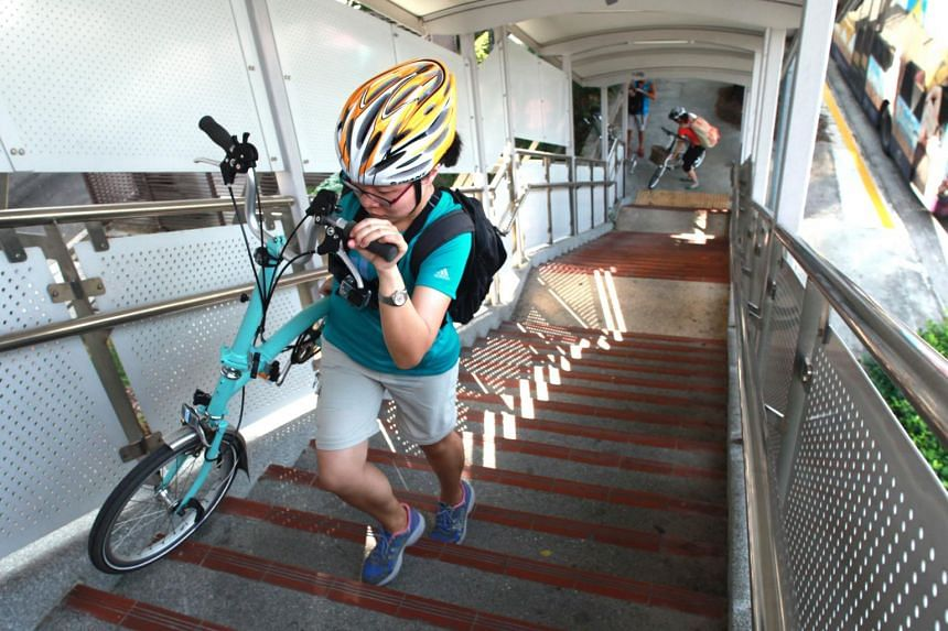 In a photo from June 18, 2015, cyclists disembark and carry their bikes across the overhead bridge over the PIE near Jalan Toa Payoh.