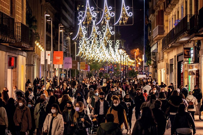 People walk on a shopping street decorated for Christmas in central Barcelona, on Nov 30, 2020.