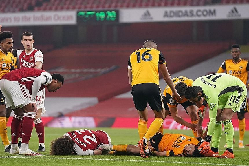 Arsenal's David Luiz and Wolves' Raul Jimenez lying on the pitch after they banged heads in the Premier League match in London on Sunday. The latest incident reignited debate about whether football is taking head collisions seriously.
