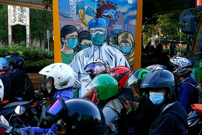 Motorcyclists passing a mural promoting awareness of the Covid-19 outbreak in Jakarta. The country remains the worst hit in South-east Asia with the number of confirmed cases at 549,508 as of yesterday, with 17,199 deaths.