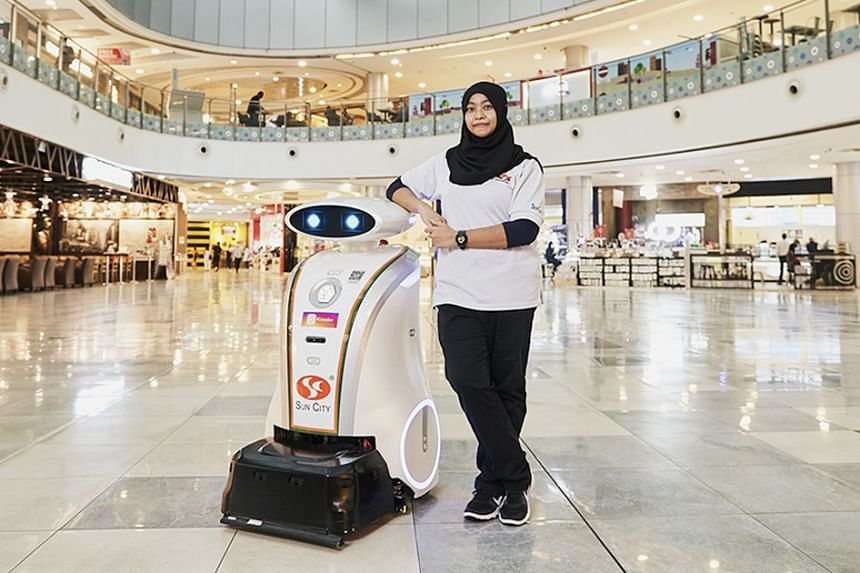 """Besides supervising a team of cleaning staff, Mdm Ainiah Mahmot, who works for Sun City Maintenance, also manages """"her baby"""", Ella, the LionsBot cleaning robot."""