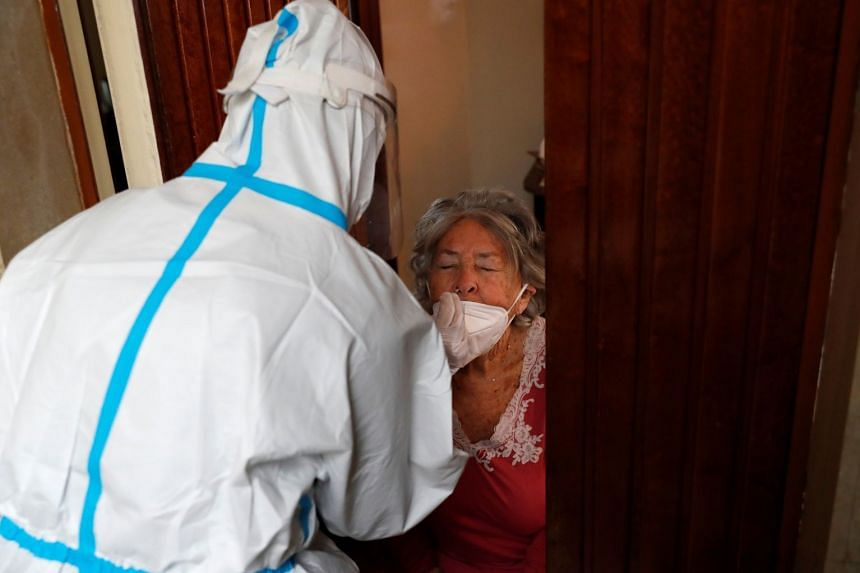 Medical workers in Rome visit the home of a patient suspected to be suffering from Covid-19 to carry out a swab test.