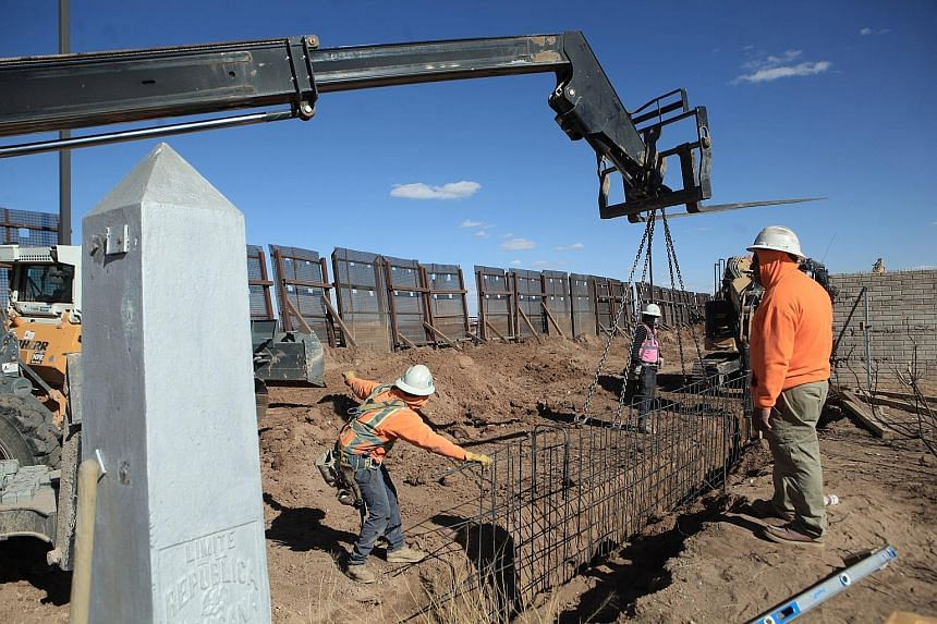 Workers rushing to finish building a metal wall between Columbus, New Mexico, in the United States, and Puerto Palomas in Chihuahua, Mexico, on Wednesday. US President Donald Trump's promise to build a wall along the US-Mexico border was the centrepi