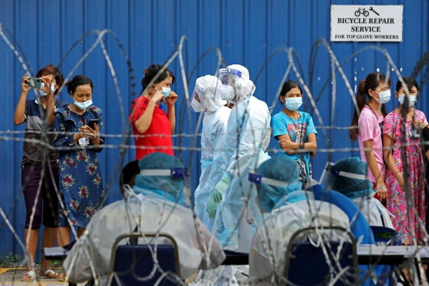 Workers wait in line to be tested for Covid-19 in Klang, Malaysia Nov 18, 2020.  Malaysia has seen a spike in foreign worker coronavirus cases due to confined and crowded spaces they live in.