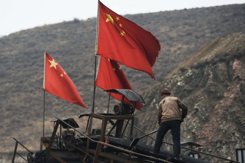 Chinese flags are seen next to a worker clearing a conveyer belt used to transport coal at a mine in China.