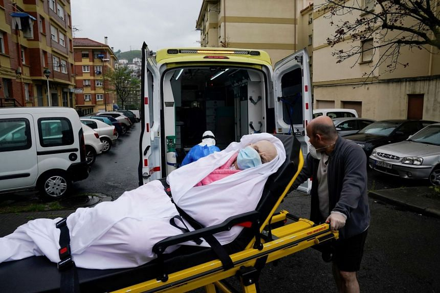 An April 2020 photo shows a 76-year-old Covid-19 patient being lifted into an ambulance by her son in Llodio, Spain.