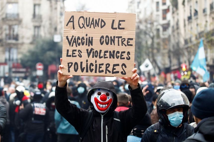 """A protester holds a placard reading """"When will there be a vaccine against police violence"""" during a demonstration in Paris, Dec 5, 2020."""