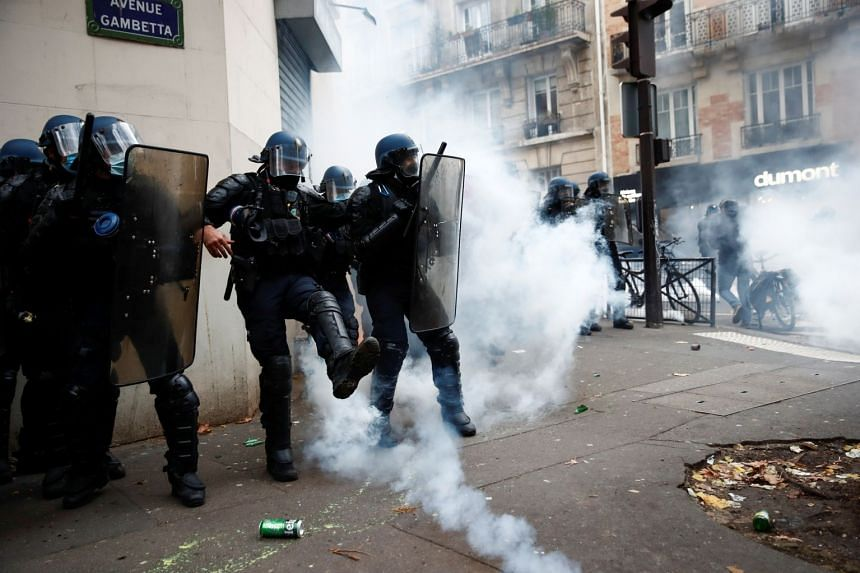 Police officers stand guard amid tear gas during a demonstration in Paris, Dec 5, 2020.