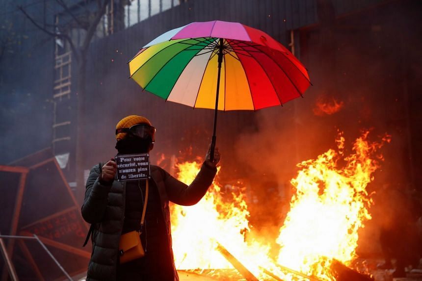 """A protester holds a sign reading """"For your safety you will have no more freedoms"""" during protests in Paris on Dec 5, 2020."""