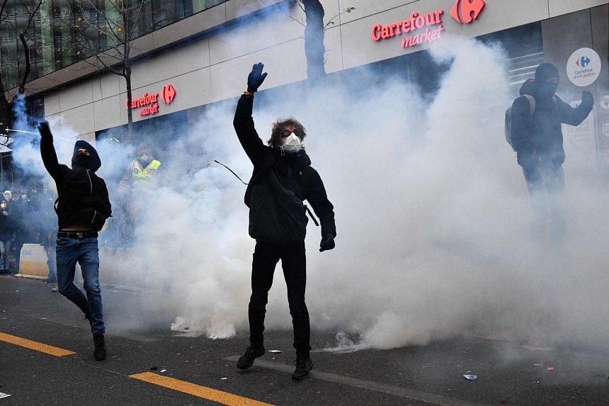 Protesters, surrounded by clouds of tear gas, throw back gas canisters during a demonstration in Paris, on Dec 5, 2020