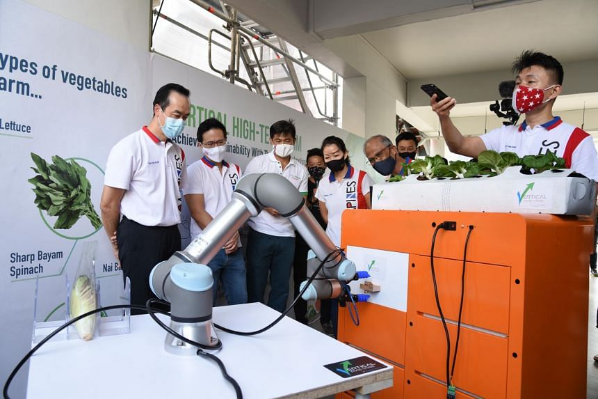 Minister for Social and Family Development Masagos Zulkifli (second right) and fellow MPs from Tampines GRC at the unveiling of a robotic arm on Dec 5, 2020.