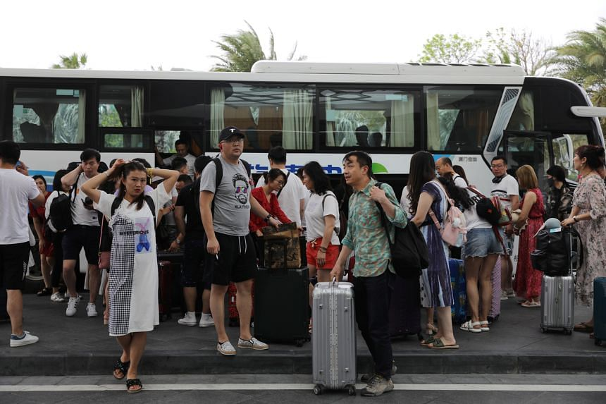 People get off a coach at an entrance of Atlantis Sanya resort in Sanya, Hainan province, on Nov 25, 2020.