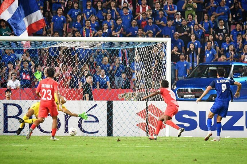 Adisak Kraisorn (right) scores a goal in the Asean Football Federation Suzuki Cup in the Rajamangala Stadium, in Bangkok, on Nov 25, 2018.