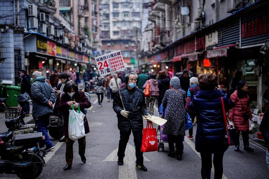 A man promoting real estate at a street market in Wuhan, on Dec 7, 2020.