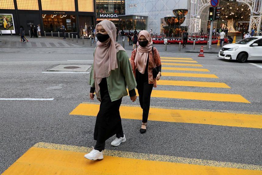 People wearing protective masks cross a street in Kuala Lumpur, Nov 30, 2020.