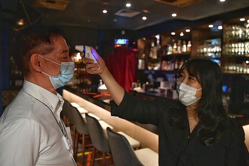 Cuppage Plaza's Bell Bar owner Mabel, who wanted to be known by only one name, taking the temperature of customer Fujita Koichi yesterday. ST PHOTO: CHONG JUN LIANG