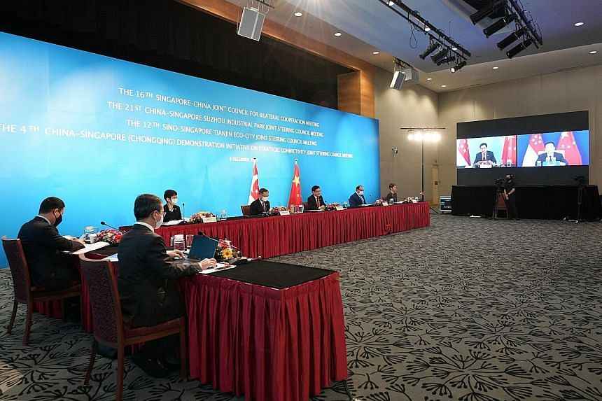 Deputy Prime Minister Heng Swee Keat co-chairing the meetings yesterday with Chinese Vice-Premier Han Zheng (on screen). With Mr Heng are (facing the camera, from left) Minister for Sustainability and the Environment Grace Fu, Health Minister Gan Kim