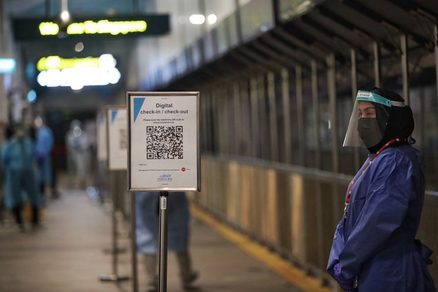 Staff directing passengers to scan a TraceTogether QR code and take a rapid antigen test after disembarking from the Quantum of the Seas, on Dec 9, 2020.