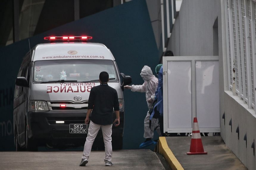 A passenger clad in white PPE from the Royal Caribbean's Quantum of the Seas being assisted into an ambulance at Marina Bay Cruise Centre on Dec 9, 2020.