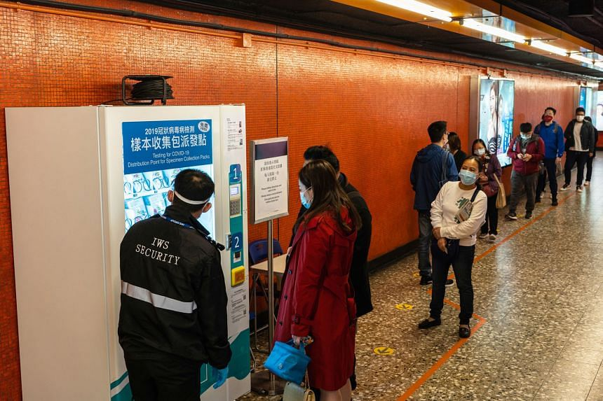 People queueing to collect Covid-19 test kits (below) from a vending machine at a train station on Hong Kong yesterday. From tomorrow till Dec 23, there will be no dine-in services between 6pm and 4.59am the next day. Businesses such as gyms, sports