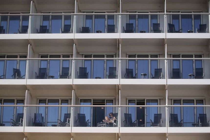 A passenger on the balcony of a room on the Quantum of the Seas, which is berthed at Marina Bay Cruise Centre after its return on Dec 9, 2020.