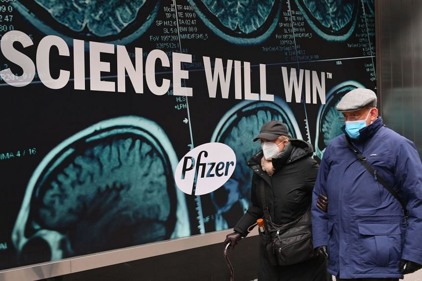 An elderly couple wearing protective face masks walk past Pfizer headquarters on Dec 9, 2020 in New York City.