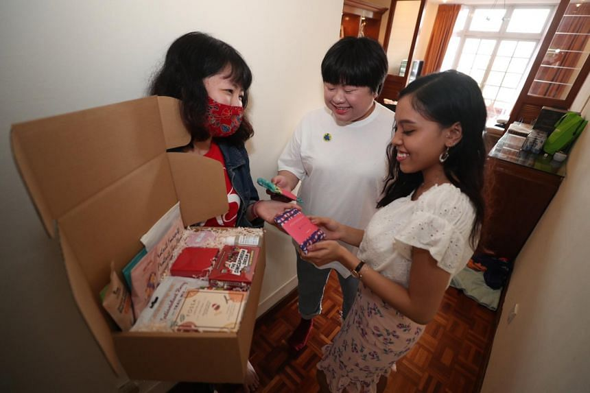 (From left) Minnie Bui delivers a gift box to her customers Eunice Chong and Nur Amira Sukiman.