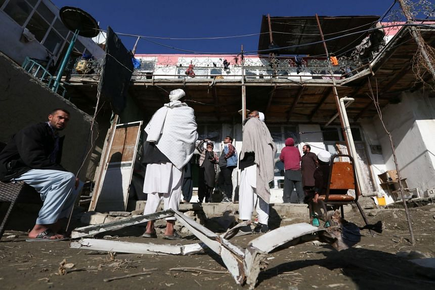 Afghan men gather at the site of a rocket attack at a residential house in Kabul on Dec 12, 2020.